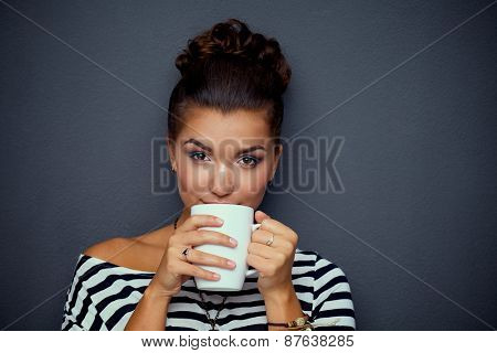 Portrait of a young woman with cup of tea or coffee.