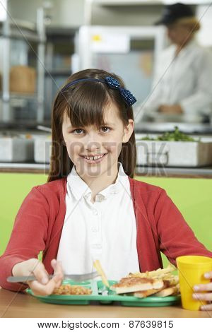 Female Pupil Sitting At Table In School Cafeteria Eating Unhealthy Lunch