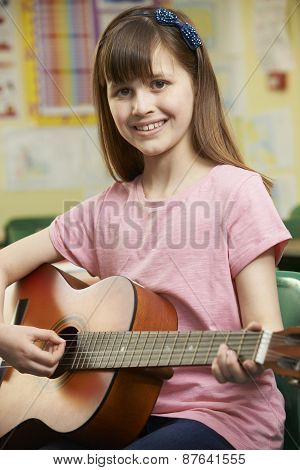 Girl Learning To Play Guitar In School Music Lesson