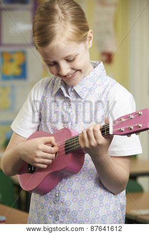 Girl Learning To Play Ukulele In School Music Lesson