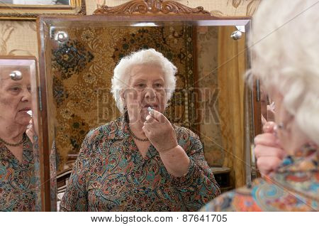 Senior Woman Puts On Lipstick