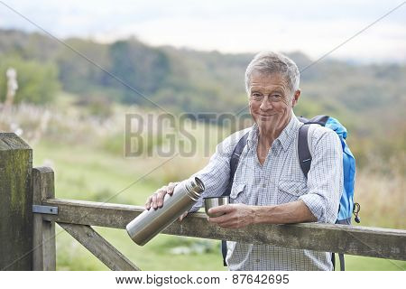 Senior Man Having Drink From Flask Whilst On Walk