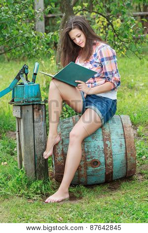 Barefoot Brunette Girl Sitting On Old Vintage Blue Wooden Barrel With Book
