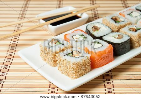 Sushi Assortment On White Dish Over Bamboo Background.