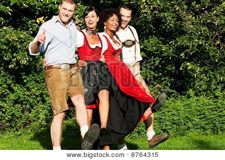 Group of four friends in Bavarian Tracht dancing