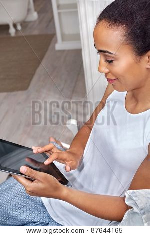 woman relaxing on sofa couch reading email on tablet computer wifi connection at home