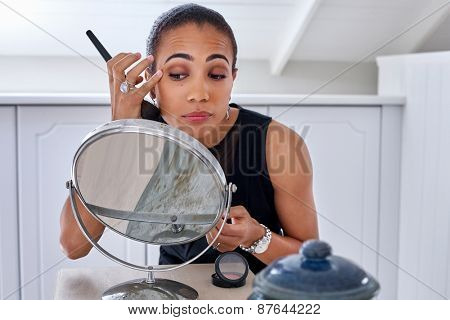young professional business women applying makeup cosmetics early morning bedroom bathroom at home