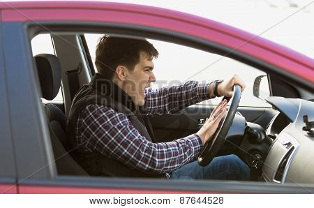 Portrait Of Aggressive Male Driver Honking In Traffic Jam