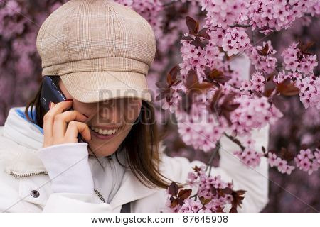 Young Woman With Hat Talking On The Phone In Outdoors