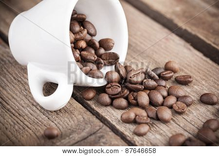 Coffee beans and cup on wooden background