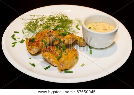 fried chicken wings served with source on white plate isoalted over black
