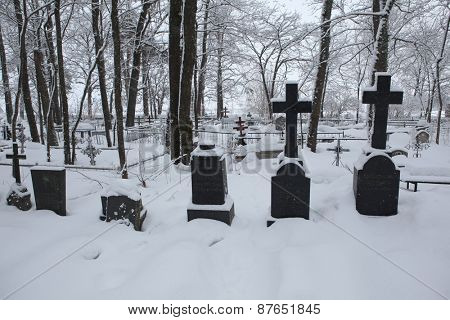 IZBORSK, RUSSIA - JANUARY 21, 2011: Snow-covered tombstones at the old cemetery in the town of Izborsk near Pskov, Russia.