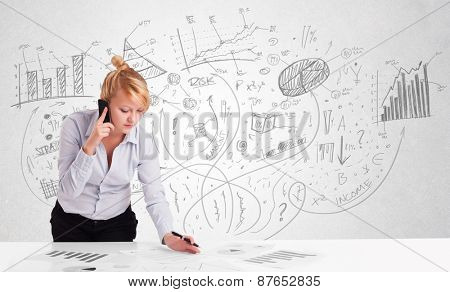 Business woman at desk with hand drawn charts at the background