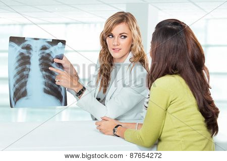 Young Female Doctor Explaining Diagnosis To Her Female Patient