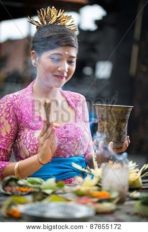 Young Balinese woman praying in traditional ceremonial clothing