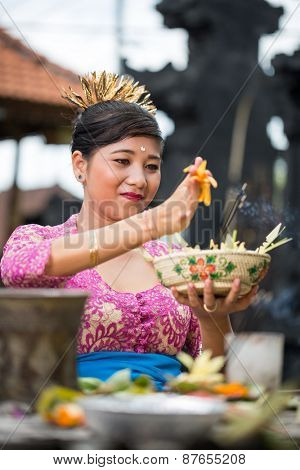 Balinese woman in temple with offering for Gods, Bali , Indonesia