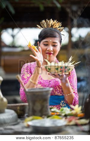 woman holding  offering for gods and praying in Bali temple