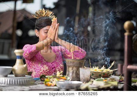 Beautiful Asian woman prays in the temple. Bali. Indonesia