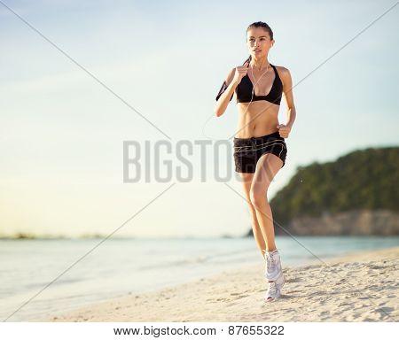 Young athlete female runs along the beach