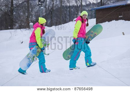 SOCHI, RUSSIA - FEBRUARY 26, 2014: Two girls go with snowboards in hand at the ski resort.