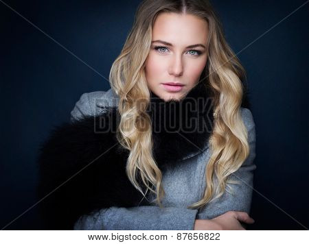 Portrait of beautiful gorgeous woman with natural makeup  wearing stylish coat with fur scarf over black background, fashion and vogue concept