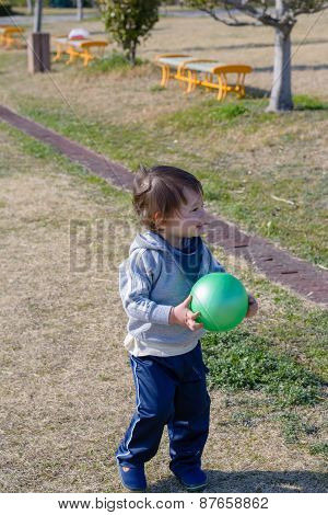 Boy Holding Ball In Playground