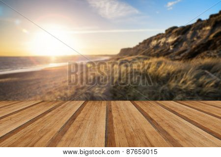 Landscape Vivid Sunset Over Beach And Cliffs With Added Lens Flare Effect With Wooden Planks Floor