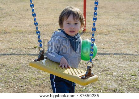 Cute Boy With Ball Near Swing