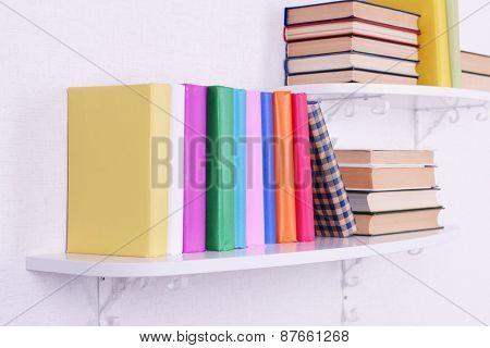 Books on shelves on white wall background