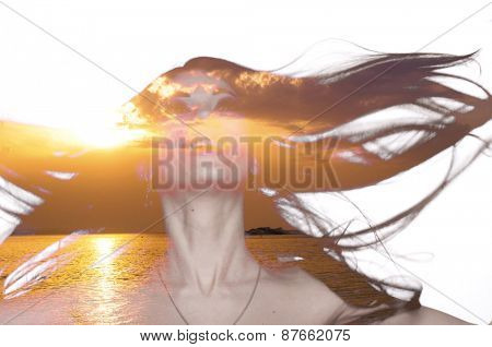 Double exposure photo of a young woman with fluttering hair and sunset over sea