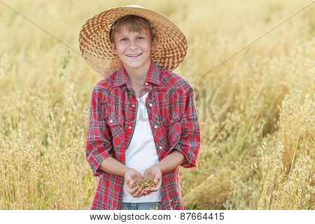 Portrait Of Smiling Teenage Farm Boy Is With Oat Seeds In Cupped Palms At Ripe Field