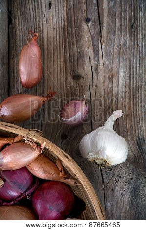 Onions And Garlic In The Basket On A Dark Wood