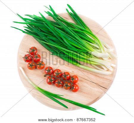 Green onion and cherry on wooden platter.