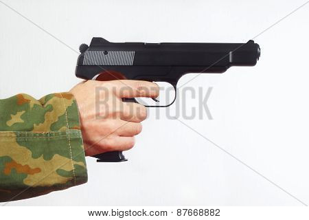 Hand in camouflage uniform with a semi-automatic gun on white background