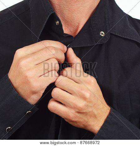 Hands a man fastened the buttons on the black shirt closeup