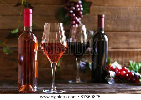 Bottles and glasses of wine with grape on wooden background