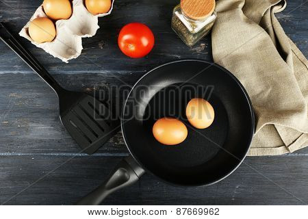 Still life with eggs and pan on wooden table, top view