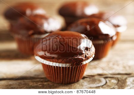 Tasty homemade chocolate muffins on wooden table
