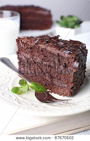 Sliced tasty chocolate cake in plate on wooden table, closeup