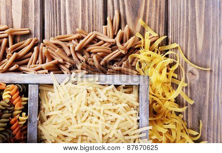 Different types of pasta in box on wooden background
