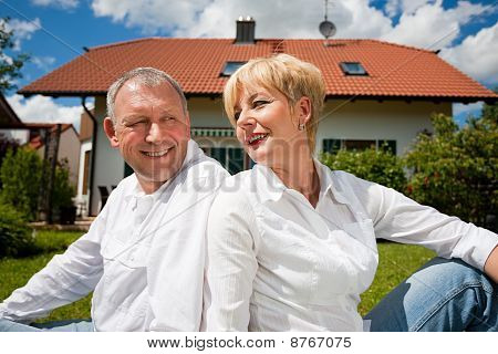 Senior couple sitting in front of their home