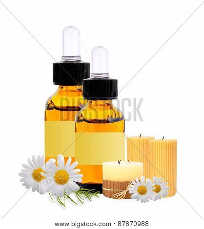 Bottles With Essence Oil, Candles And Chamomiles Isolated On White