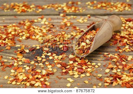 Milled Chili  Peppers Flakes And Corns On Wooden Board