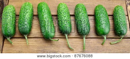 Fresh Seven Cucumbers On The Rough Wood Background