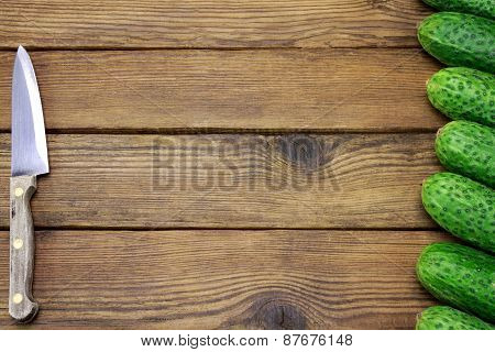Fresh Seven Cucumbers And Kitchen Knife On The Rough Wood Background