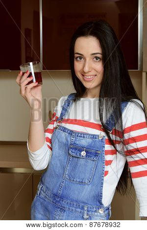 Brunette Housewife In Blue Overalls Holding A Glass Of Juice And Smiling.