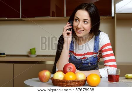 Brunette Housewife In Blue Overalls Talking On The Phone Smiling.