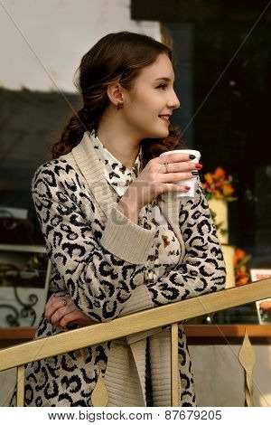 Girl Drinking Coffee On The Street And Smiling Looking Away