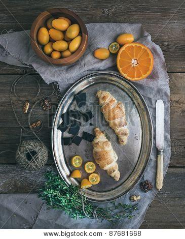 Rustic Breakfast Set: Chocolate Croissants On Metal Dish, Fresh Kumquats, Orange Half, Walnuts, Thym