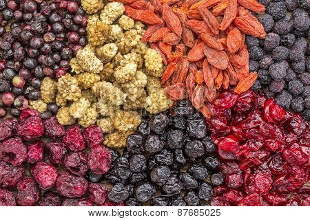 background of healthy dried superfruit berries - blueberry, mulberry, cherry, goji, elderberry, chokeberry, and cranberry